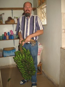 Mark with a bunch of Matooke (cooking bananas)